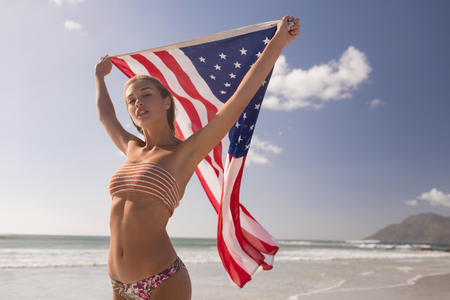 Foto de Low angle view of young woman holding waving American flag at beach on a sunny day - Imagen libre de derechos