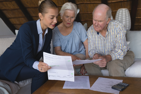 Photo for Front view of a female doctor and senior couple looking and discussing over medical reports they hold in their hands at home - Royalty Free Image