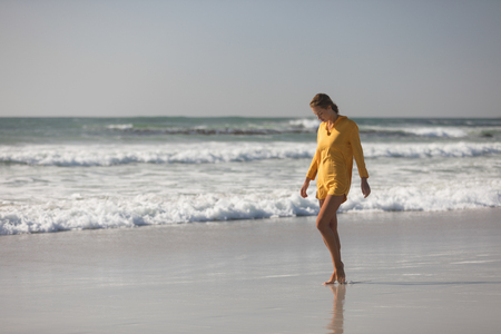Photo for Young woman walking on the beach near seashore - Royalty Free Image
