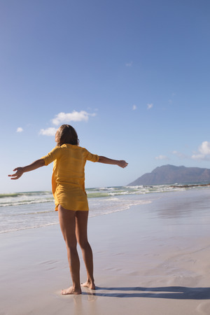 Photo for Rear view of woman standing with arms outstretched at beach in the sand - Royalty Free Image