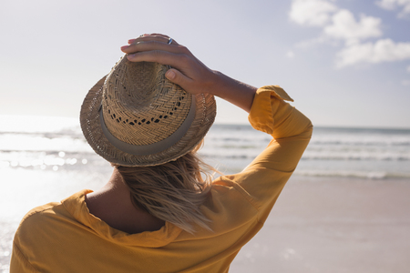 Photo for Rear view of woman wearing hat standing on the beach towards ocean - Royalty Free Image