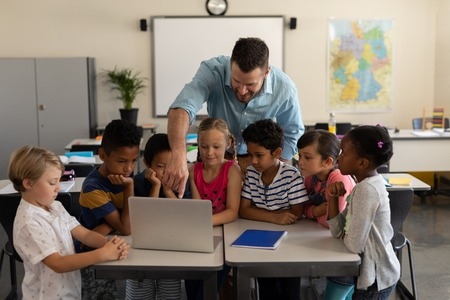Photo pour Front view of a male teacher teaching kids on laptop in classroom of elementary school - image libre de droit