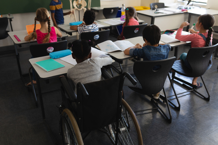 Rear view of disable schoolboy with classmate studying and sitting at desk in classroom of elementary school