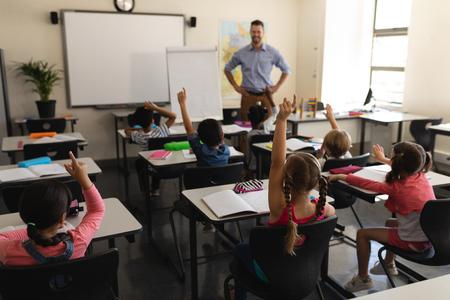 Photo pour Rear view of school kids raising hand in classroom of elementary school - image libre de droit
