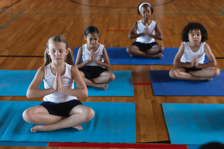 Photo pour Front view of schoolkids doing yoga and meditating on a yoga mat in school - image libre de droit