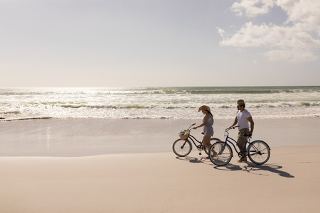 Photo for Side view of young couple with bicycle standing on beach in the sunshine - Royalty Free Image