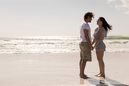 Photo pour Side view of romantic young couple holding hands and looking each other on beach in the sunshine - image libre de droit