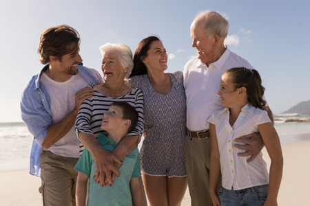 Photo for Front view of happy multi-generation family looking each other on beach in the sunshine - Royalty Free Image