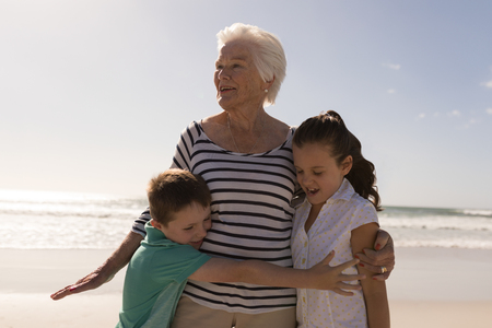 Photo pour Front view of happy multi-generation family embracing on beach in the sunshine - image libre de droit