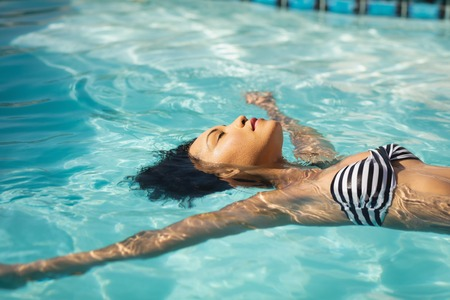 Photo pour Side view of young mixed-race woman floating in swimming pool in backyard of her home - image libre de droit