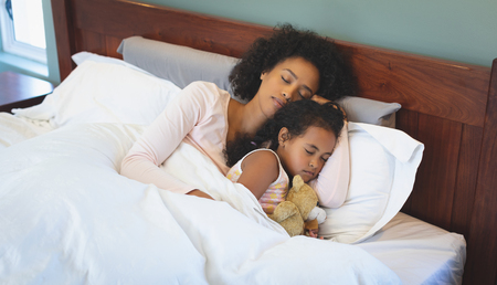 Photo for High angle view of African American mother and daughter sleeping together on bed in bedroom at home - Royalty Free Image