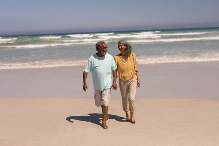 Photo pour Front view of happy senior couple holding hands and walking on beach in the sunshine - image libre de droit