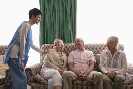 Front view of female doctor interacting with happy senior people on the sofa in living room at home