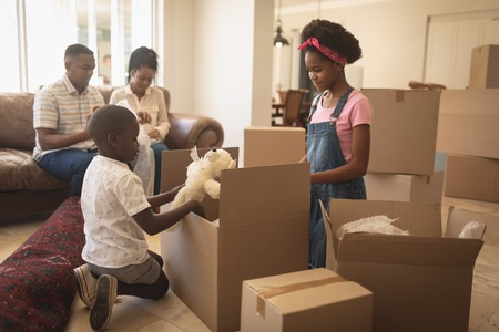 Photo for Side view of African American children unpacking their belongings and parents sitting on sofa at home - Royalty Free Image