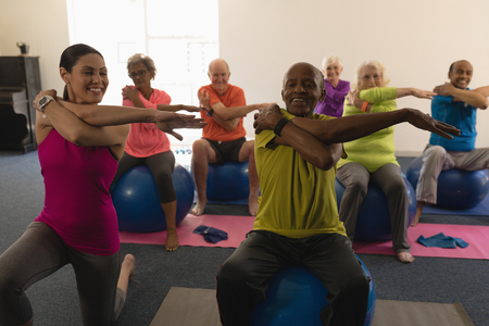 Photo for Front view of senior people exercising with female trainer in fitness studio - Royalty Free Image
