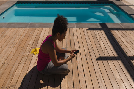 Photo for Side view of woman using her mobile phone while sitting in the backyard of home - Royalty Free Image