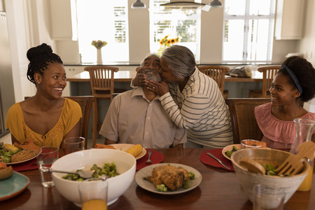 Photo pour Front view of African American senior woman kissing her husband surrounded by his daughter and his grand daughter at the dining table at home - image libre de droit