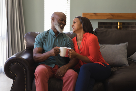 Photo for Front view of active senior couple having coffee while sitting on the sofa in living room at home - Royalty Free Image