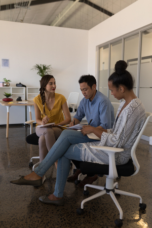 Photo for Side view of diverse business colleagues discussing plans while writing on a diary in modern office - Royalty Free Image