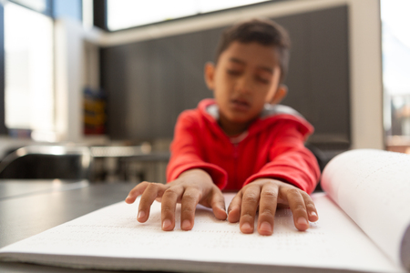 Photo pour Front view of blind mixed-race schoolboy hands reading a braille book at desk in a classroom at elementary school - image libre de droit