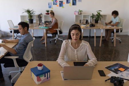 Photo for Front view of pretty Caucasian businesswoman working on laptop at her desk with multi-ethnic coworkers working hard in the background - Royalty Free Image