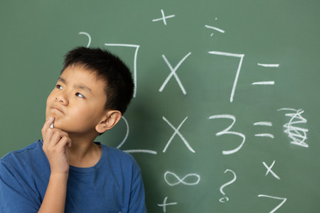 Photo pour Front view of thoughtful Asian schoolboy doing math on green chalkboard in a classroom at elementary school - image libre de droit