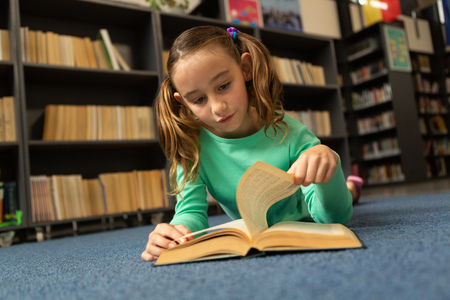 Photo for Front view of Caucasian schoolgirl lying on floor and turning a page in a book in library at elementary school - Royalty Free Image