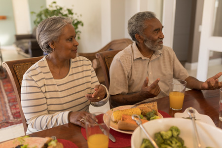 Front view of a senior African American couple sitting together on dining table at home