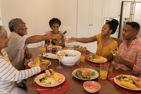 Photo pour Front view of a happy multi-generation African American family having meal together and grandfather is pouring wine on dining table at home - image libre de droit