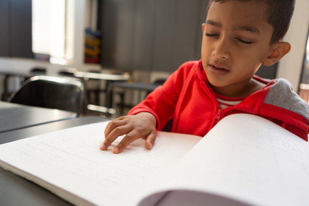 Photo pour Front view of blind mixed-race schoolboy reading a braille book at desk in a classroom at elementary school - image libre de droit