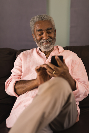 Photo for front view of an active African American senior man using mobile phone while sitting on a sofa in living room at home - Royalty Free Image