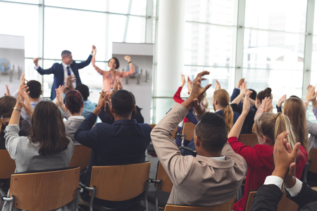 Photo pour Rear view of diverse business people applauding and celebrating while they are sitting in front of multi-ethnic business coworkers at business seminar in office building - image libre de droit