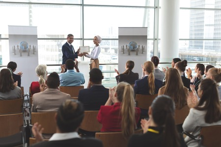 Photo pour Front view of mixed race businesswoman receiving award from mixed race businessman in front of business professionals applauding at business seminar in office building - image libre de droit