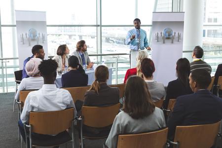 Foto de Front view of African-American businessman speaker speaking in a business seminar in modern office building - Imagen libre de derechos