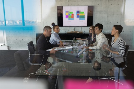 Photo for High view of sitting mixed race business people having discussion in a meeting at modern office. They work hard - Royalty Free Image
