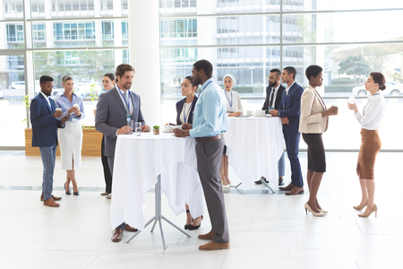 Photo for Front of view of diverse business people interacting with each other at table in office lobby - Royalty Free Image