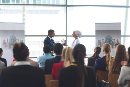 Photo for Front view of mixed race businesswoman receiving award from mixed race businessman in front of business professionals sitting at business seminar in office building - Royalty Free Image