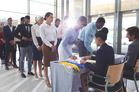 Photo pour Front view of pretty Caucasian businesswoman and handsome African American businessman signing in at conference registration table while group of diverse business people standing in queue in lobby - image libre de droit