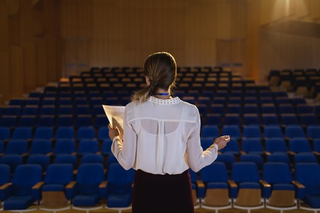 Foto de Rear view of beautiful Caucasian businesswoman practicing and learning script while standing in the auditorium - Imagen libre de derechos