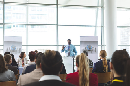 Photo for Front view of African-American businessman speaker speaking in a business seminar in modern office building - Royalty Free Image