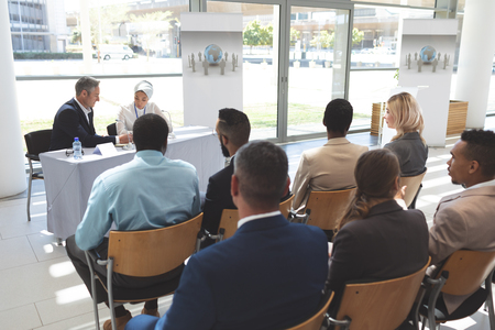Photo pour Rear view of diverse business people chatting while attending a business seminar in office building - image libre de droit