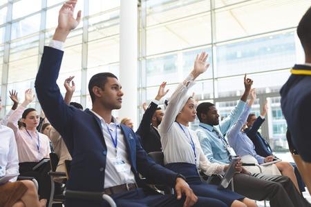 Photo pour Side view of diverse business people raising hands in business seminar in office building - image libre de droit
