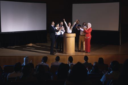 Photo pour Front view of happy Caucasian businesswoman standing at the stage of the auditorium with colleagues in front of audience - image libre de droit