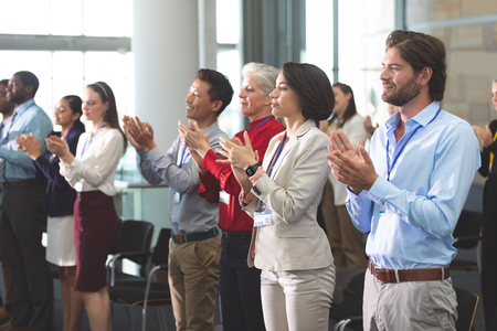 Photo pour Side view of diverse business people applauding standing at a business seminar in office building - image libre de droit