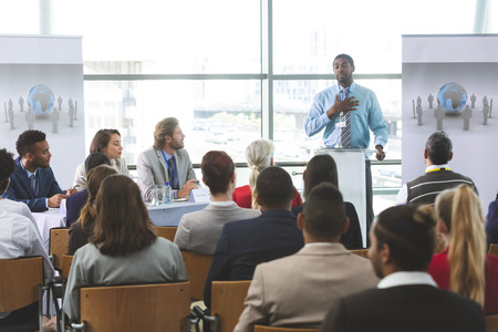 Photo pour Front view of African-American businessman speaker speaking in a business seminar in modern office building - image libre de droit