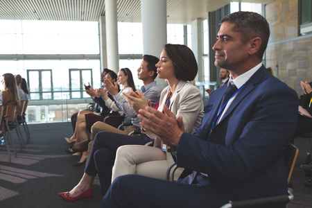 Photo pour Side view of diverse business people clapping at a business seminar in office building - image libre de droit