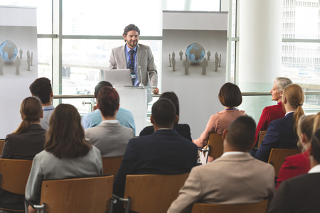 Photo pour Front view of Caucasian businessman with laptop speaks in front of diverse group of business people sitting at business seminar in office building - image libre de droit
