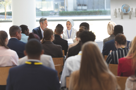Photo pour Rear view of group of diverse business people attending a business seminar in office building - image libre de droit