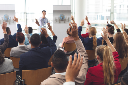 Foto de Rear view of diverse business people raising hands while they are sitting in front of Asian businessman at business seminar in office building - Imagen libre de derechos