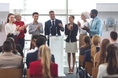 Foto de Front view of diverse group of business professionals standing on podium while speaking in front of business people at business seminar in office building - Imagen libre de derechos